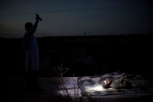 A man points a flashlight towards the body of a Syrian man killed by Syrian army shelling at a graveyard, in Aleppo, Syria, Oct. 13, 2012.