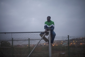 Un migrante guineano que encaramado en la valla tras las devoluciones en caliente que se han producido minutos antes, El tambien fue devuelto a Marruecos.