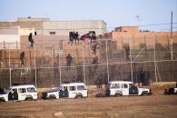 La Guardia Civil española sube por la valla para obligar a los migrantes subsaharianos a bajar y devolverlos a Marruecos posteriormente.