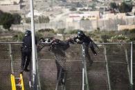 Ante la negacion del migrante a bajar de la valla para evitar ser devuelto en caliente, la Guardia Civil escala y con el uso de la fuerza le obligan a bajar.