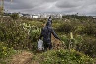 Un grupo de subsaharianos regresa al asentamiento con la comida que han recoido de la basura del mercado.